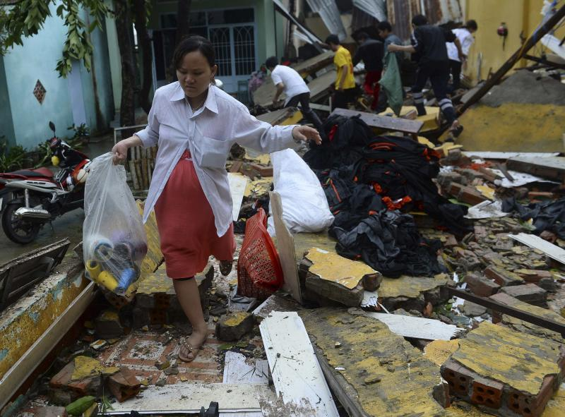 Ngoc Chau carries belongings through remains of her home, which collapsed because of Typhoon Nari, in Vietnam's central Quang Nam province