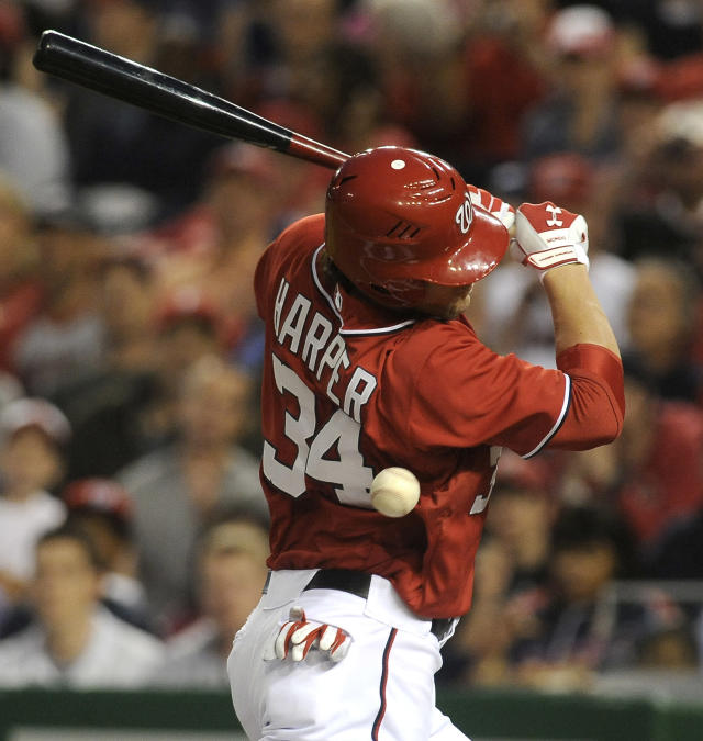 Washington Nationals' batter Bryce Harper is hit by the pitch thrown by Philadelphia Phillies pitcher Cole Hamels during the first inning of their baseball game at Nationals Park, Sunday, May 6, 2012, in Washington. Harper later scored by stealing home from third base. (AP Photo/Richard Lipski)