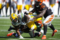 Green Bay Packers running back A.J. Dillon (28) dives for yardage is he is tackled by Cincinnati Bengals linebacker Germaine Pratt (57) in the second half of an NFL football game in Cincinnati, Sunday, Oct. 10, 2021. (AP Photo/AJ Mast)