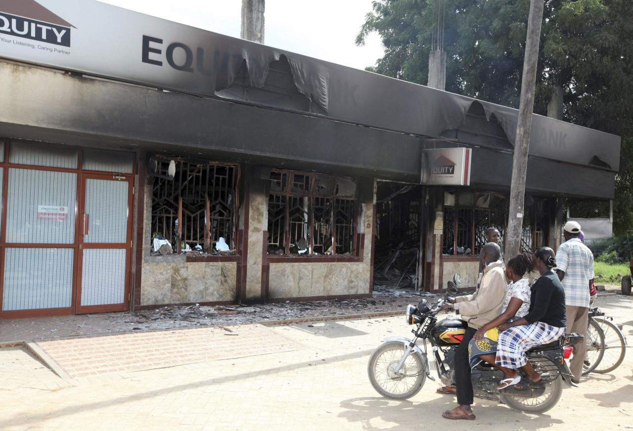 Residents of Mpeketoni view the damage left behind at the Equity bank after unidentified gunmen attacked the coastal Kenyan town of Mpeketoni, June 16, 2014. At least 48 people were killed and others wounded when more than two dozen unidentified gunmen attacked a coastal Kenyan town overnight, police and the Kenya Red Cross said on Monday. 