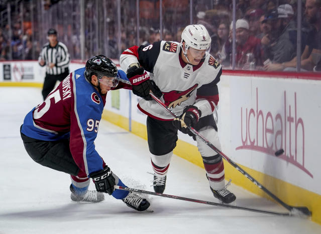 Arizona Coyotes defenseman Jakob Chychrun (6) and Colorado Avalanche left wing Andre Burakovsky (95) chase the puck along the boards during the second period of an NHL hockey game, Saturday, Oct. 12, 2019, in Denver. (AP Photo/Jack Dempsey)