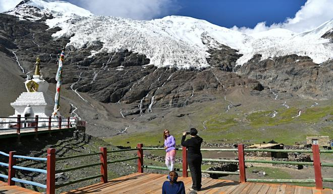 "A tourist poses for photos at the Karuola Glacier scenic area in southwest China's Tibet autonomous region. China says the region is open to all foreigners, but the US found that Beijing has ""systematically impeded travel"" for diplomats and journalists. Photo: Xinhua"