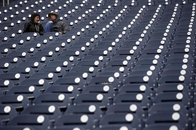 Alli Engle and Adam Noll, both from Arlington, Va., sit in the rain before an exhibition baseball game between the Washington Nationals and the Detroit Tigers at Nationals Park Saturday, March 29, 2014, in Washington. The game was canceled due to weather. (AP Photo/Alex Brandon)