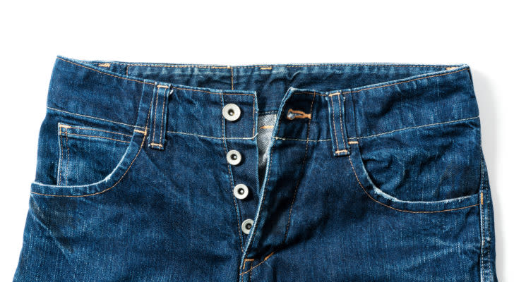 Button fly jeans placed on a white background