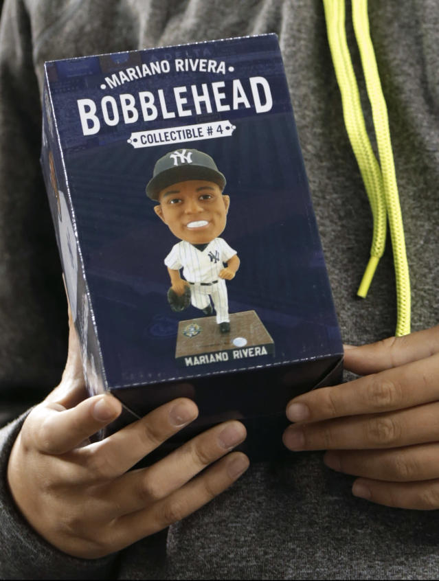 A youngster displays a Mariano Rivera bobblehead doll, after turning in a voucher to get it at the New York Yankees' baseball game against the Tampa Bay Rays, Tuesday, Sept. 24, 2013, in New York. (AP Photo/Kathy Willens)