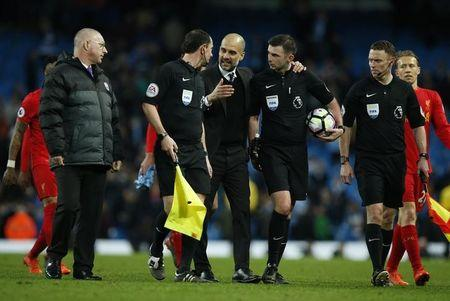 Manchester City manager Pep Guardiola speaks with referee Michael Oliver after the game