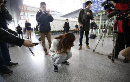 ournalists attempt to interview a woman who is the relative of a passenger on Malaysia Airlines flight MH370, as she crouches on the floor crying, at the Beijing Capital International Airport in Beijing March 8, 2014. REUTERS/Kim Kyung-Hoon