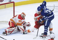 Toronto Maple Leafs centre Auston Matthews (34) gets tied up by Calgary Flames defenseman Mark Giordano (5) as Flames goaltender David Rittich (33) keeps a close eye on the loose puck during third period NHL hockey action in Toronto on Monday, Feb. 22, 2021. (Nathan Denette/The Canadian Press via AP)