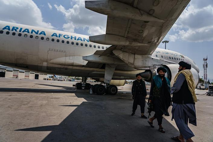 Taliban fighters stand beside a jetliner on the tarmac