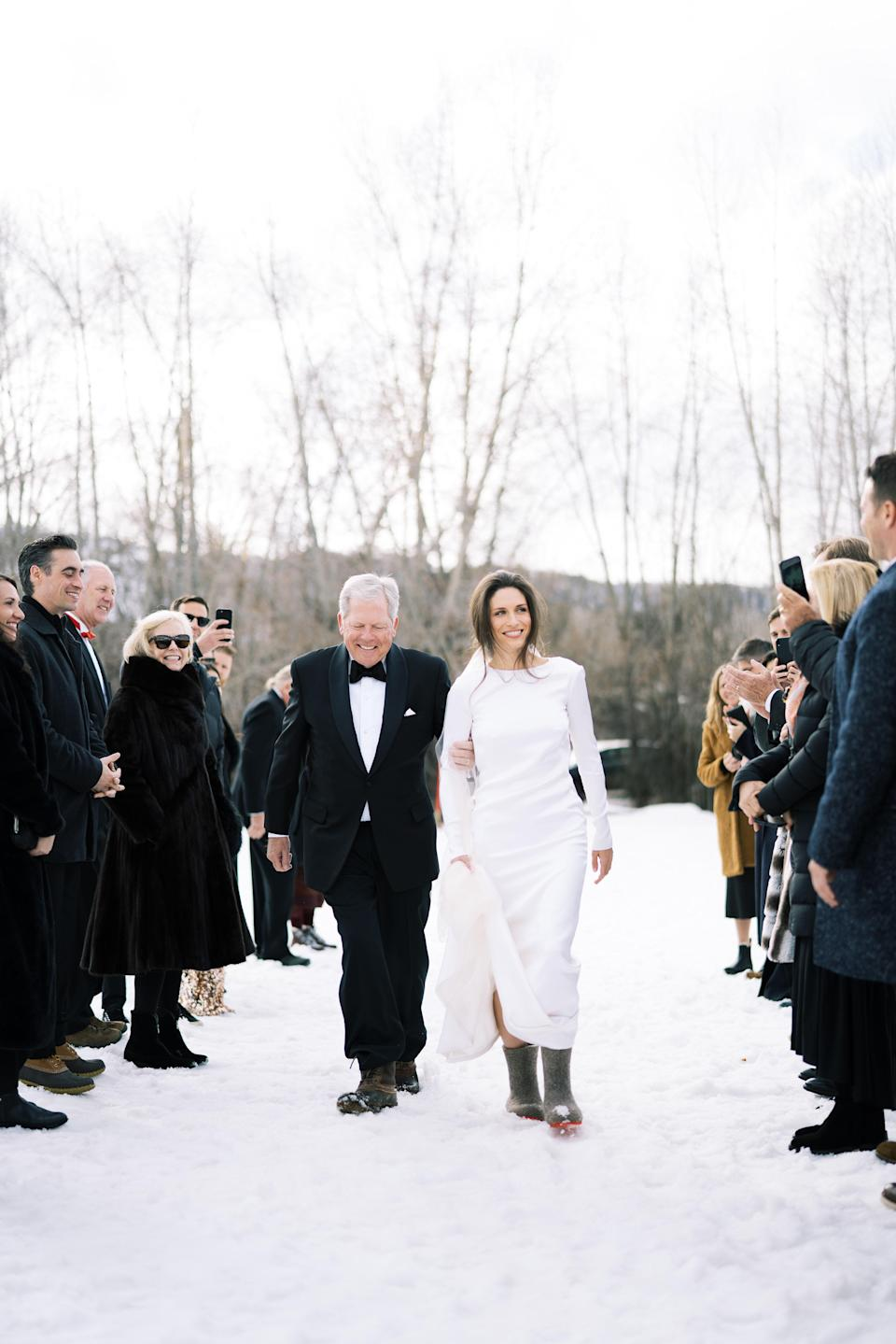"""My father walking me down the aisle and making sure I don't fall down on the way to the altar. Peter is 6'4"""" and I am 5'6""""—I would have never thought that I would """"walk down the aisle"""" in flat felted wool boots, but here I am. I don't think I felt elegant until I slipped into my gray velvet Manolos just prior to the start of the reception. Nonetheless, I loved this meadow and the afternoon light we got for the ceremony; it was beautiful."""