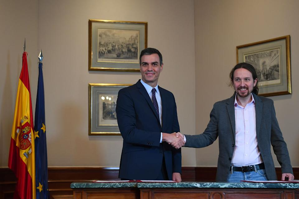 """Spanish incumbent prime minister Pedro Sanchez (L) and the leader of the left-wing electoral alliance """"Unidas Podemos"""" Pablo Iglesias (R) shake hands after a press conference in Madrid on November 12, 2019, after announcing an agreement to form a governement two days after a repeat general election. (Photo by GABRIEL BOUYS / AFP) (Photo by GABRIEL BOUYS/AFP via Getty Images)"""