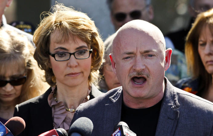 FILE - In this March 6, 2013 file photo, former Rep. Gabrielle Giffords, left, listens to her husband Mark Kelly, right, during a return to the supermarket where she was wounded in a rampage two years ago in Tucson, Ariz. Kelly went to a Tucson gun store a week ago to buy a .45-caliber handgun and a military-style rifle the day before the appearance. It didn't take long for the purchase to draw criticism from gun-rights supporters. (AP Photo/Ross D. Franklin, File)