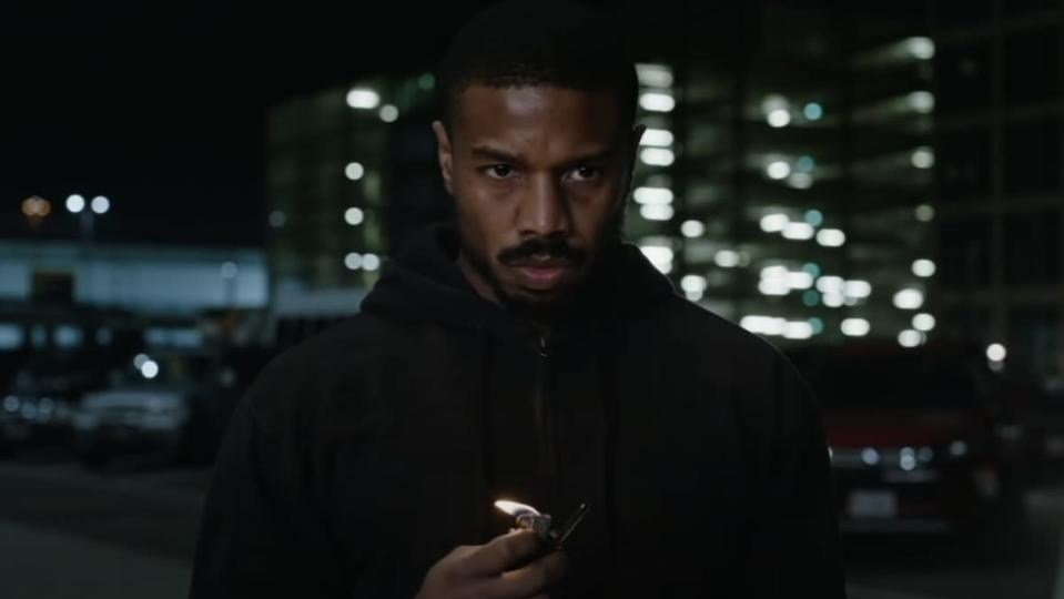 Michael B. Jordan wearing all black at night and holding a lighter that is lit in Amazon Prime Video's Without Remorse