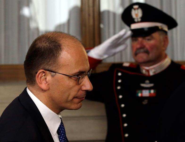"""Italian Democratic Party lawmaker Enrico Letta is saluted by a presidential guard as he leaves after making a statement to the media after talks with Italian President Giorgio Napolitano, in Rome's Quirinale presidential palace, Wednesday, April 24, 2013. Italy's president has appointed Enrico Letta as premier, asking him to try to form a government to end Italy's political paralysis and set the country back on the path of reform and economic growth. Letta, a 46-year-old longtime center-left lawmaker, told reporters Wednesday he accepted the job knowing it's an enormous responsibility and that Italy's political class """"has lost all credibility."""" (AP Photo/Gregorio Borgia)"""