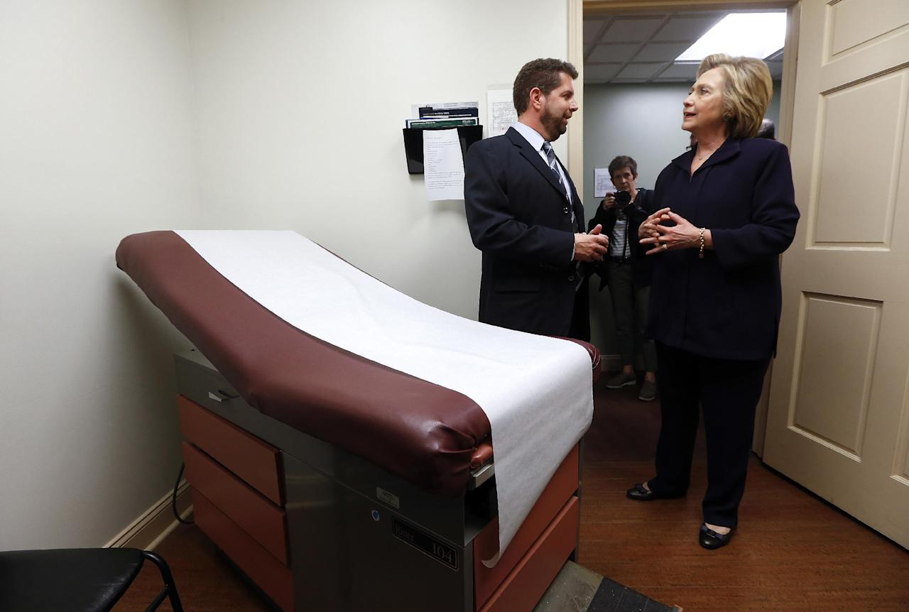 "FILE - In this May 2, 2016 file photo, Democratic presidential candidate Hillary Clinton listens to Dr. Christopher Beckett, CEO of Williamson Health and Wellness Center during a tour an exam room of the facility in Williamson, W.Va. With the hourglass running out for his administration, President Barack Obama's health care law is struggling in many parts of the country. Double-digit premium increases and exits by big-name insurers have caused some to wonder whether ""Obamacare"" will go down as a failed experiment. (AP Photo/Paul Sancya)"