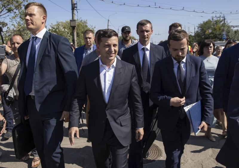 Ukrainian President Volodymyr Zelenskiy, center, walks during his visit to the Zaporizhye region, Ukraine, Thursday, July 18, 2019. Zelenskiy's party is showing the most support in opinion polls ahead of Sunday's snap parliamentary elections, but obtaining a solid majority in the Verkhovna Rada is far from certain. (Ukrainian Presidential Press Office via AP)