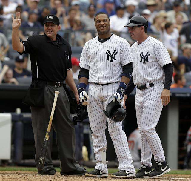 New York Yankees' Robinson Cano, center, throws his bat after disagreeing with a strike called by umpire Jeff Kellogg, left, during the fourth inning of the baseball game against the Baltimore Orioles at Yankee Stadium, Sunday, Sept. 1, 2013, in New York. (AP Photo/Seth Wenig)