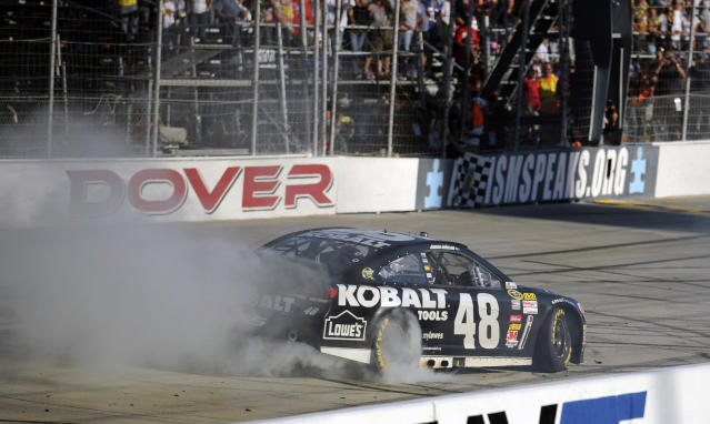 Jimmie Johnson performs a burnout after he won a NASCAR Sprint Cup Series auto race on Sunday, Sept. 29, 2013, at Dover International Speedway in Dover, Del. (AP Photo/Nick Wass)