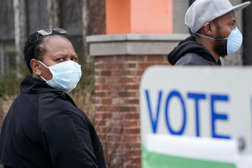 Voters masked against the coronavirus line up to vote at Riverside High School in Milwaukee. (Photo: AP Photo/Morry Gash)