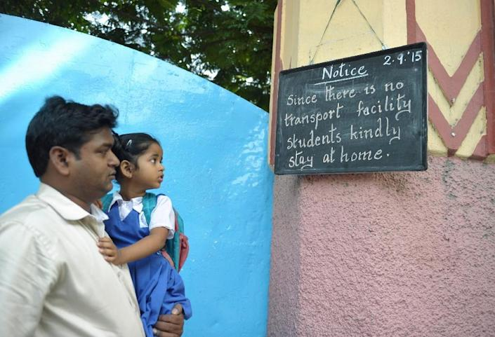 A man holds his daughter as they look at a noticeboard with information about a transport strike displayed in Secunderabad, the twin city of Hyderabad in southern India, on September 2, 2015 (AFP Photo/Noah Seelam)