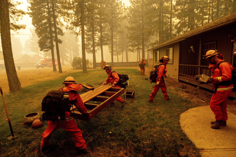 Inmate firefighters prep a home by moving combustible items as the Dixie Fire burns in Chester, Calif., on Wednesday, Aug. 4, 2021. The region is under red flag fire warnings due to dry, windy conditions. (AP Photo/Noah Berger)