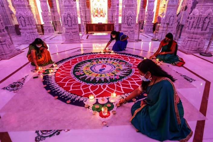 "Chino Hills, CA, Friday, November 13, 2020 - Volunteers tend to a Rangoli (sand art) dedicated ""unity and selfless service,' as part of Diwali is celebrations at BAPS Swaminarayan Mandir. (Robert Gauthier/ Los Angeles Times)"