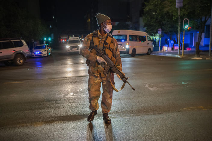 A South African soldier enforces the lockdown downtown Johannesburg, South Africa, Friday, March 27, 2020. Police and army started patrolling moments after South Africa went into a nationwide lockdown for three weeks in an effort to mitigate the spread to the coronavirus. The new coronavirus causes mild or moderate symptoms for most people, but for some, especially older adults and people with existing health problems, it can cause more severe illness or death.(AP Photo/Jerome Delay)