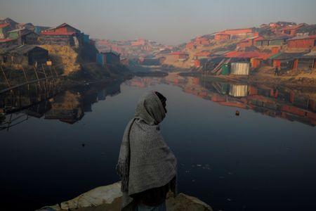 FILE PHOTO: A Rohingya refugee stands next to a pond in the early morning at the Balukhali refugee camp near Cox's Bazar
