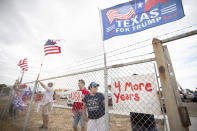 Standing at the fence, supporters of President Donald Trump display flags and signs as they wait for Air Force One to land Wednesday afternoon July 29, 2020 at Midland International Air and Space Port in Midland Texas. (Ben Powell/Odessa American via AP)