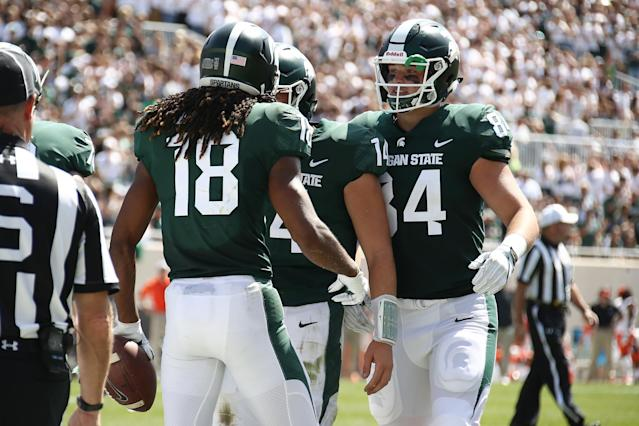 "Felton Davis III (L) of the <a class=""link rapid-noclick-resp"" href=""/ncaab/teams/may/"" data-ylk=""slk:Michigan State Spartans"">Michigan State Spartans</a> celebrates a first half touchdown at Spartan Stadium. (Getty Images)"