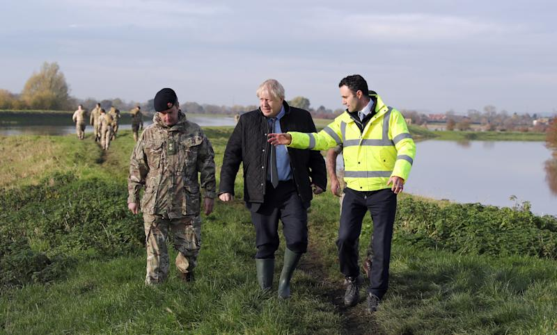 RETRANSMISSION, adding name of Environment Agency official. Prime Minister Boris Johnson walks with Lt Col Tom Robinson from the Light Dragoons and Oliver Harmar, Yorkshire Area Director of the Environment Agency, during a visit to Stainforth, Doncaster, to see the recent flooding.