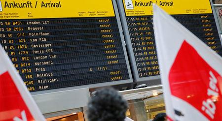 Members of Germany's Verdi union protest with flags in front of a display with canceled flights during a warning strike by ground services, security inspection and check-in staff at Tegel airport in Berlin