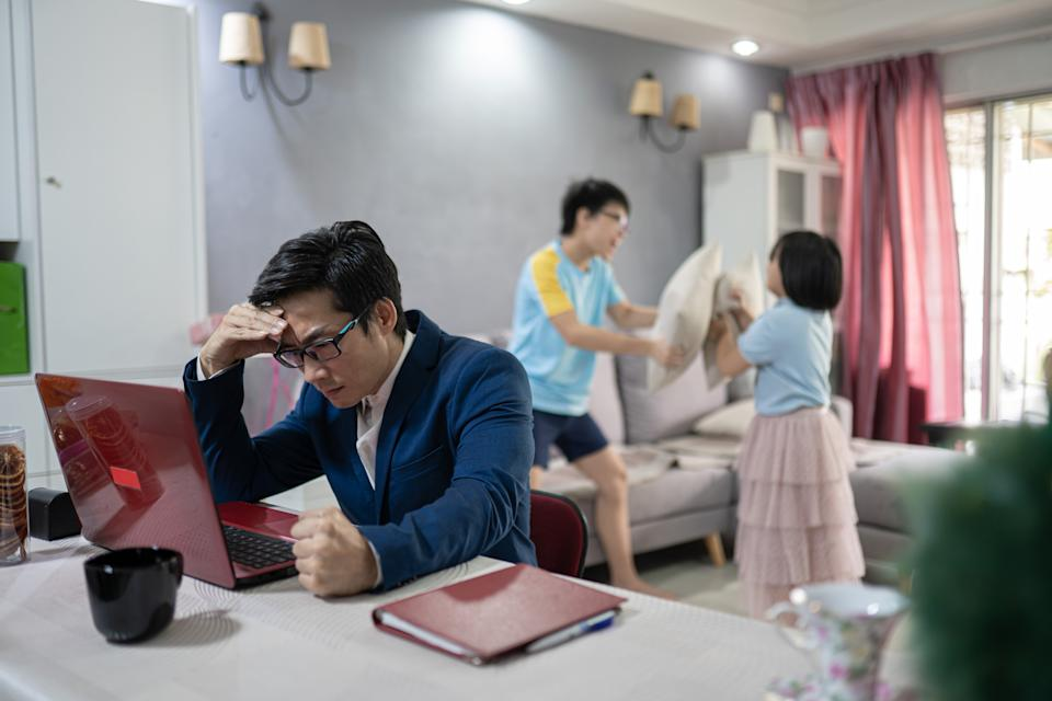 Asian Chinese man work at home. Children were having playing in pillow fights. Father loss concentration and frustrated.