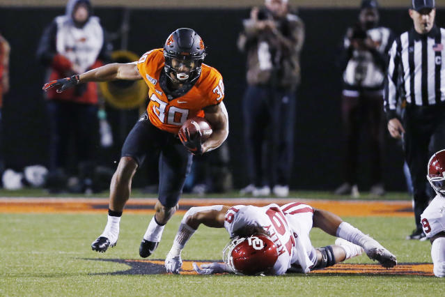 Oklahoma State running back Chuba Hubbard (30) avoids a tackle by Oklahoma linebacker Caleb Kelly (19) in the first half of an NCAA college football game in Stillwater, Okla., Saturday, Nov. 30, 2019. (AP Photo/Sue Ogrocki)