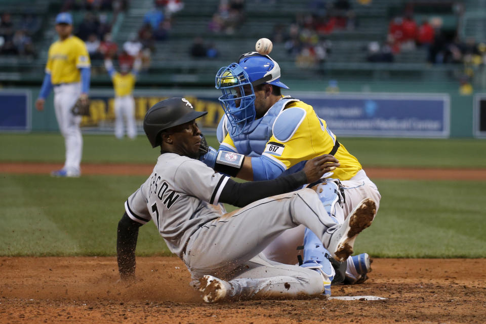 Boston Red Sox catcher Kevin Plawecki, right, cannot catch a throw from the outfield as Chicago White Sox's Tim Anderson slides in to score during the seventh inning of a baseball game, Saturday, April 17, 2021, in Boston. (AP Photo/Mary Schwalm)