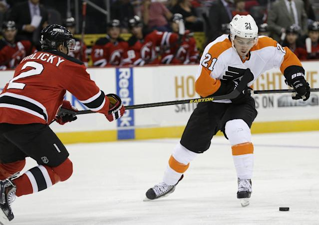 Philadelphia Flyers center Scott Laughton (21) skates against New Jersey Devils defenseman Marek Zidlicky (2), of the Czech Republic, during the first period of an NHL hockey game, Thursday, Sept. 26, 2013, in Newark, N.J. (AP Photo/Julio Cortez)