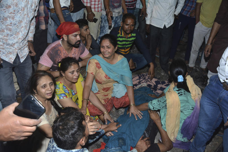 Relatives mourn by the body of a victim of a train accident in Amritsar, India, Friday, Oct. 19, 2018. A speeding train ran over a crowd watching fireworks during a religious festival in northern India on Friday, killing at least 50 people, a Congress party leader said. (AP Photo/Prabhjot Gill)