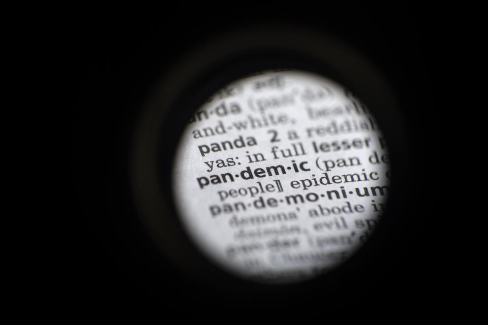 """In this Saturday, Nov. 21, 2020, photo taken through a camera lens the word """"pandemic"""" in seen in a dictionary in Washington. Dictionary.com declared """"pandemic"""" its 2020 word of the year. (AP Photo/Jenny Kane)"""