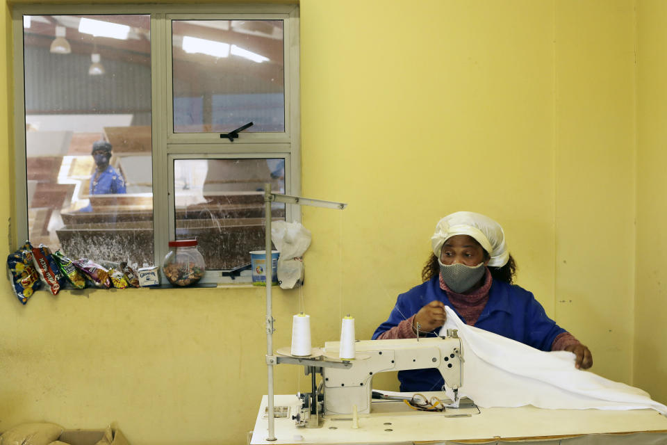 "A worker sews lining for a coffin at Enzo Wood Designs, in Johannesburg, Wednesday, Sept. 30, 2020. Casey Pillay, a coffin-maker in South Africa, watched the coronavirus pandemic turn his business upside down. For Pillay, the need for coffins rose and fell as South Africa's lockdown levels changed, but overall, he said, ""business went down."" As the world surpasses 1 million deaths, Africa is bracing for a likely second wave of infections. (AP Photo/Themba Hadebe)"
