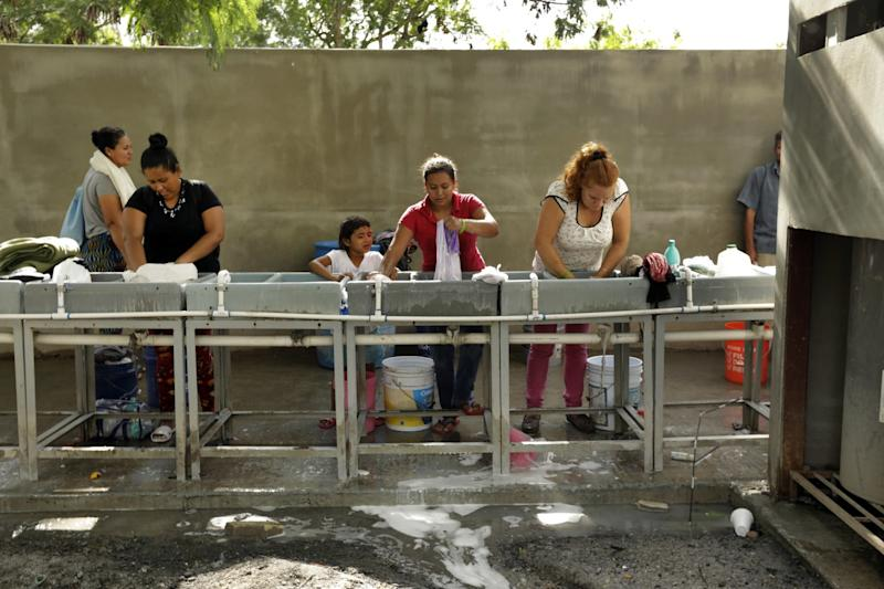 Migrants wash their clothes in a facility at the Matamoros refugee camp