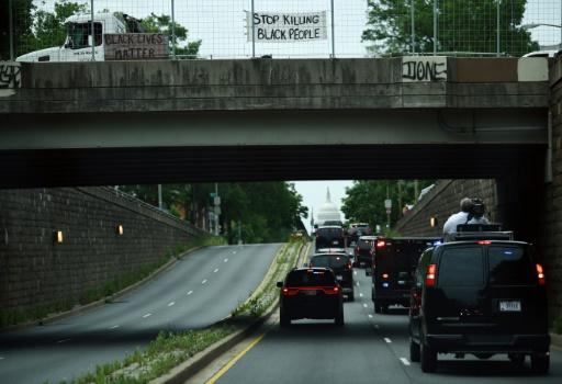 Protesters display signs over President Donald Trump's motorcade in Washington, DC