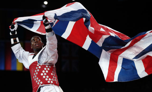 Britain's Muhammad Lutalo looks back at the Union flag he is carrying as he celebrates winning his men's -80kg bronze medal taekwondo match against Armenia's Arman Yeremyan at the London Olympic Games at the ExCeL venue August 10, 2012. REUTERS/Darren Staples (BRITAIN - Tags: SPORT OLYMPICS SPORT TAEKWONDO TPX IMAGES OF THE DAY)