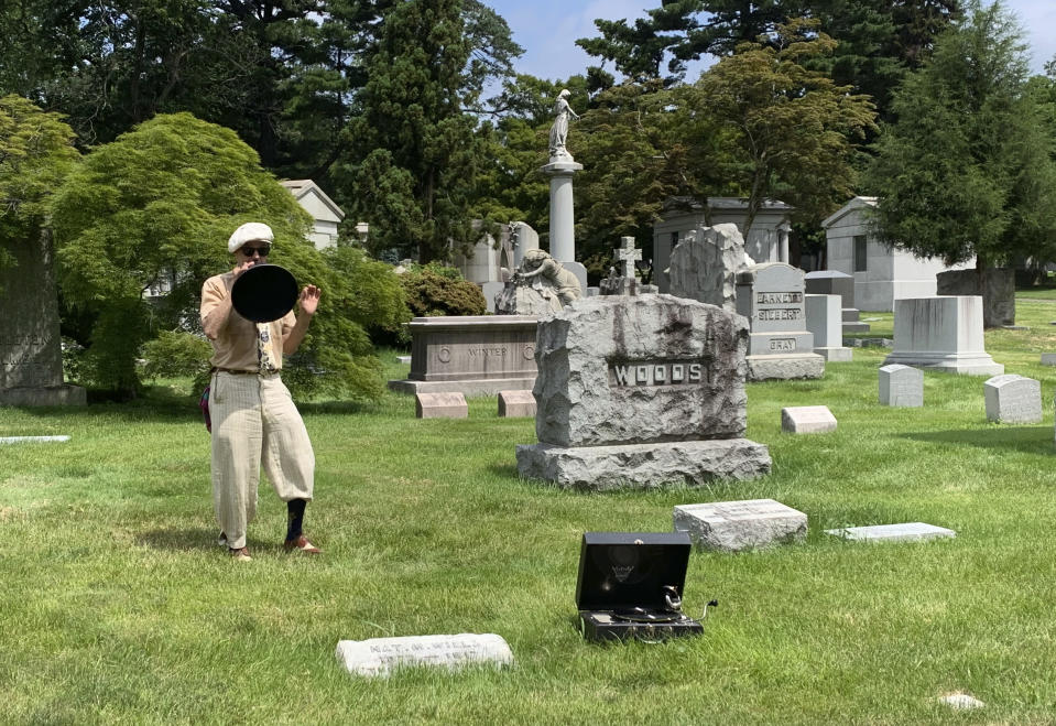 """Michael Cumella, aka DJ MAC, speaks through a vintage megaphone near the gravesite of Nat M. Wills, a vaudeville star of the early 20th century known as """"The Happy Tramp"""" at Woodlawn Cemetery in the Bronx on June 27, 2021. Wills was among the jazz and vaudeville greats included on a tour led by Cumella. (AP Photo/Julia Rubin)"""