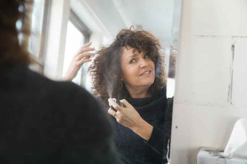 Mature woman applying hair spray to her lustrous mane in front of mirror.