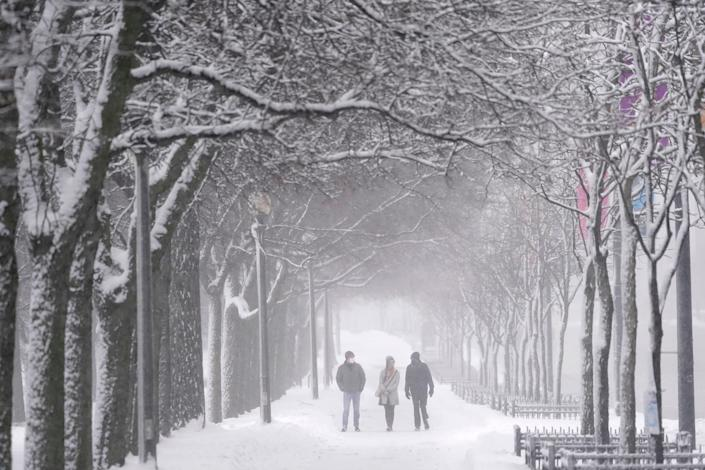 Pedestrians stroll down a snow covered sidewalk Sunday, Jan. 31, 2021, in Chicago's Grant Park, as light snow falls during day two of a winter storm that was expected to dump nearly one foot of snow in the greater Chicago area.