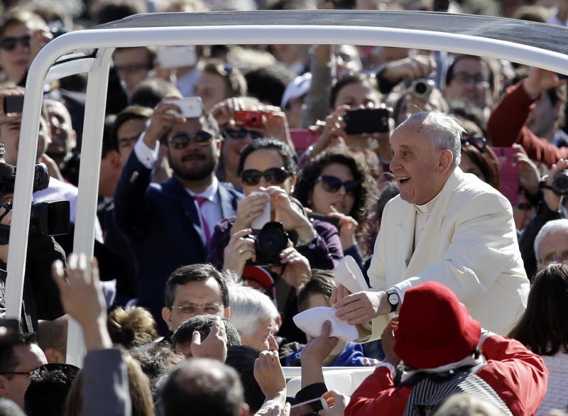 Pope Francis exchanges a skull cap with a participant in the audience as he tours with his pope mobile St. Peter's Square at the Vatican , Wednesday, April 16, 2014. (AP Photo/Gregorio Borgia)
