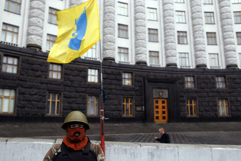 A protester guards the Ukrainian government building in Kiev, Ukraine, Sunday, Feb. 23, 2014. The Kiev protest camp at the center of the anti-President Viktor Yanukovych movement filled with more and more dedicated demonstrators Sunday morning setting up new tents after a day that saw a stunning reversal of fortune in a political standoff that has left scores dead and worried the United States, Europe and Russia. (AP Photo/ Marko Drobnjakovic)