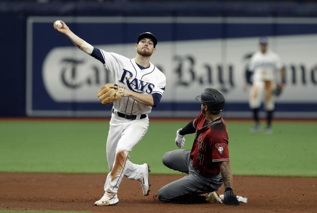 Tampa Bay Rays second baseman Brandon Lowe, left, forces Arizona Diamondbacks' Ketel Marte at second and relays the throw to first in time to turn a double play on Wilmer Flores during the fifth inning of a baseball game Wednesday, May 8, 2019, in St. Petersburg, Fla. (AP Photo/Chris O'Meara)