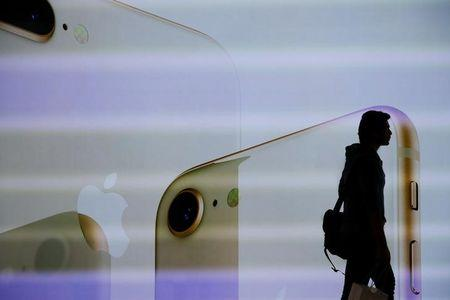 A customer walks past a large screen at the new Apple Visitor Center in Cupertino