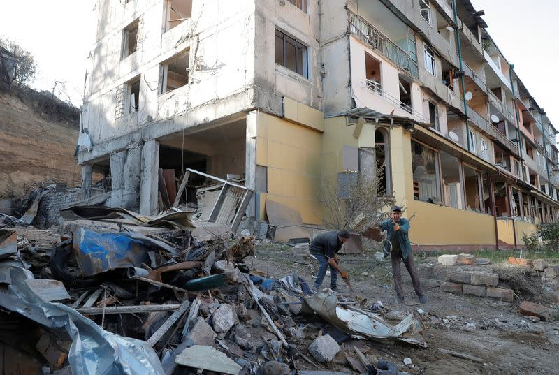 Workers remove debris near a residential building, which was damaged during the military conflict over the breakaway region of Nagorno-Karabakh, in Stepanakert